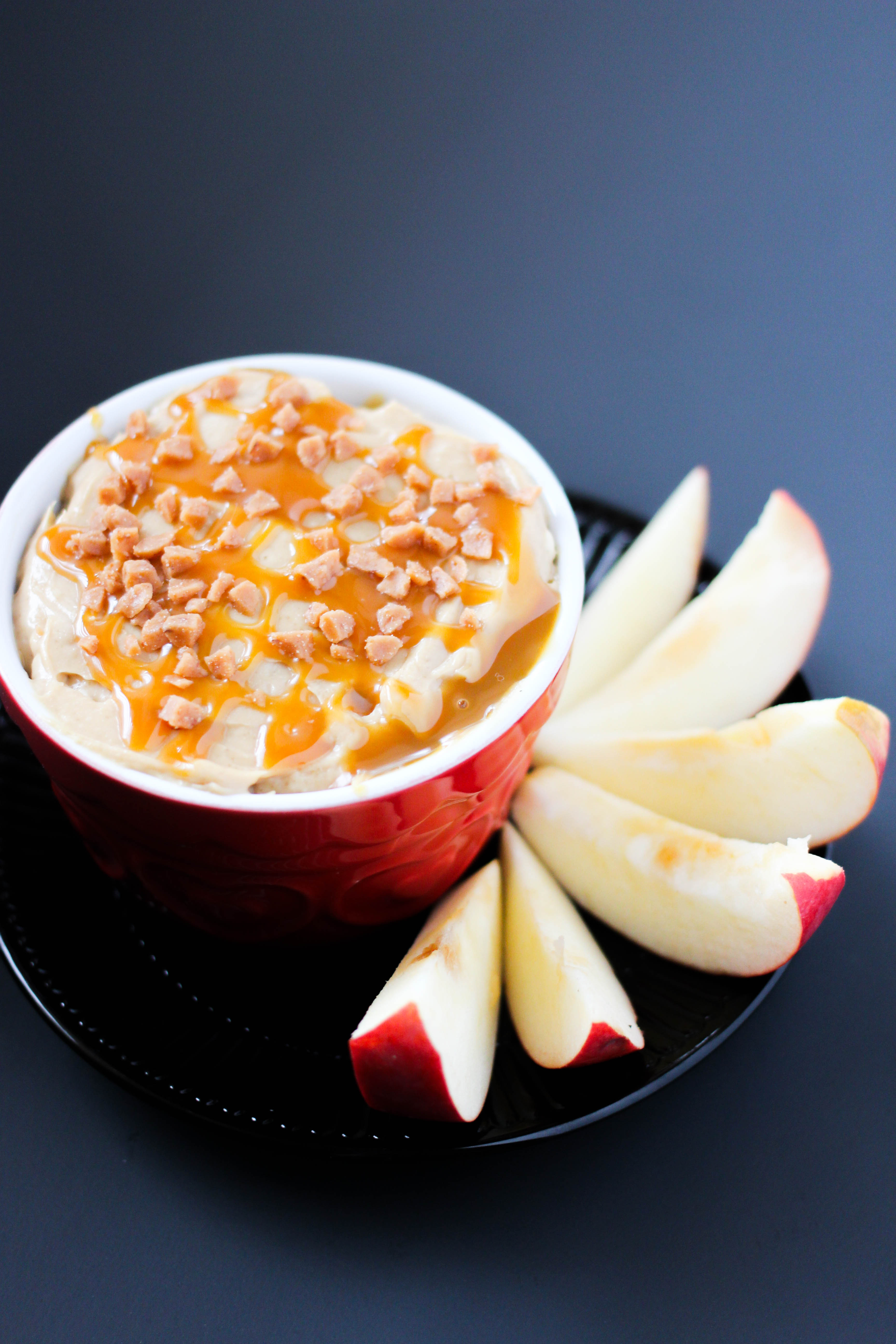 caramel apple dip on a black plate with apples