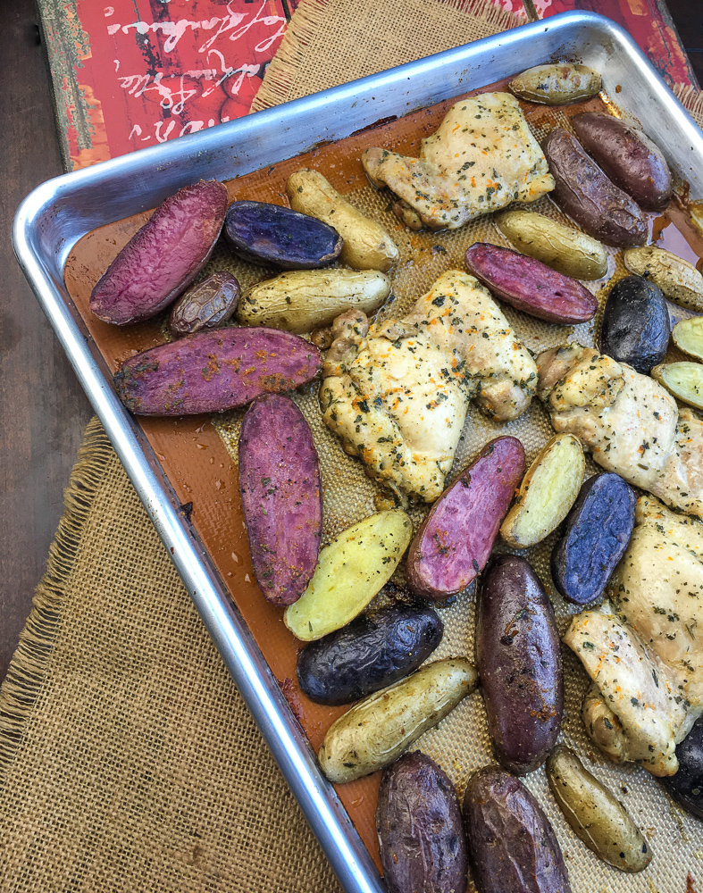 Marinated Baked Chicken Thighs with Fingerling Potatoes on a baking sheet
