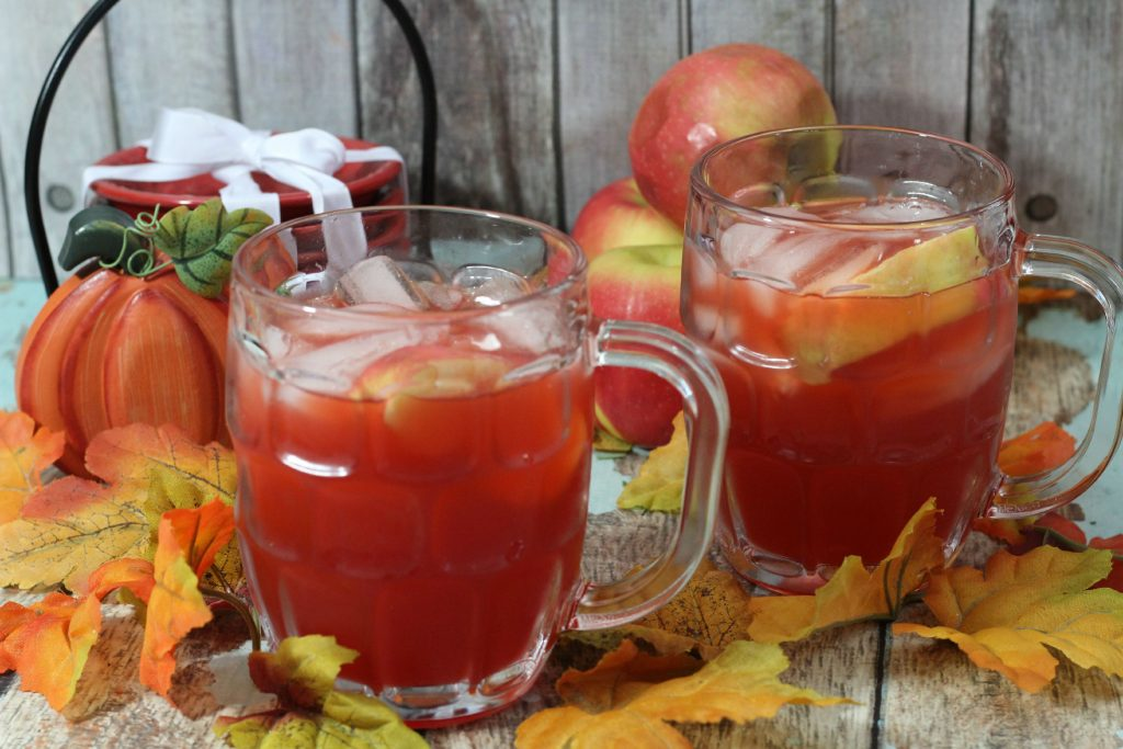apple cider cocktail with leaves around the glasses